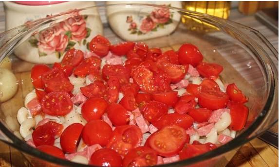 3. Дальше измельчаем колбасу, и половину выкладываем поверх макарон. Дальше - порезанные помидоры. Дальше - опять слой макарон.