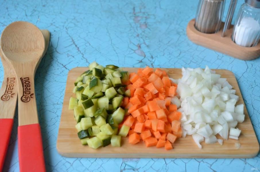 2. Порежьте лук, морковь и огурцы кубиками. Обжарьте на растительном масле сначала лук, потом через пару минут положите морковь, и через пару минут огурчики. Жарьте еще минут 5.