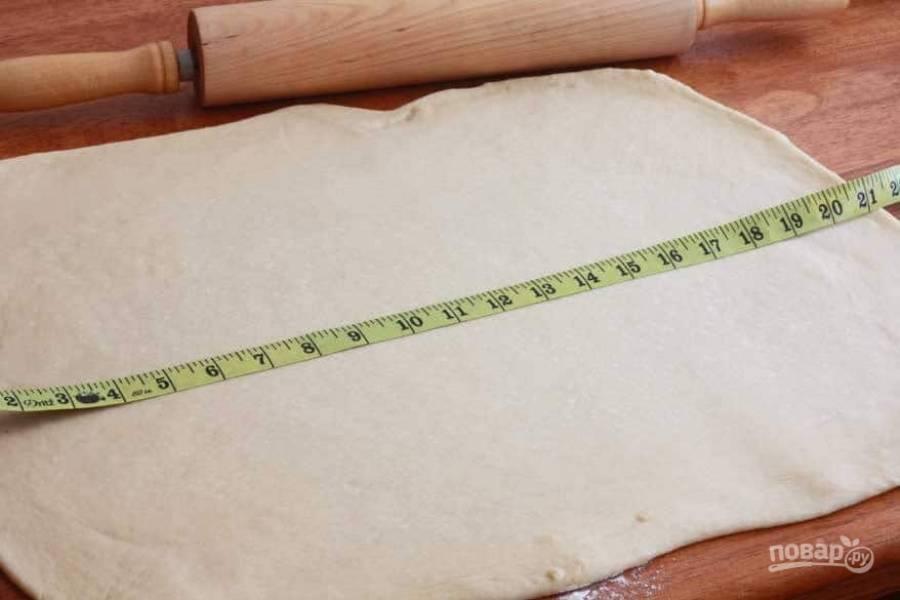 7.Переложите тесто на ровную, заранее посыпанную мукой поверхность и раскатайте его в прямоугольник.