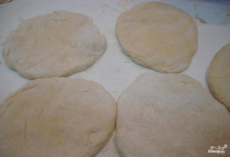 После того, как тесто подойдет, раскатайте его, щедро присыпав мукой. Вырежете стаканом кружочки или же раскатайте тесто колбаской, отрезайте одинаковые квадраты и формируйте лепешки вручную.