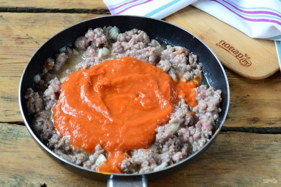 Добавьте в сковороду томатный соус, перемешайте, убавьте огонь и готовьте 5-7 минут.