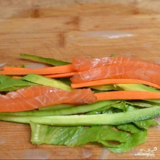 Аккуратно сложите небольшую часть ингредиентов (все сразу - морковь, огурцы, авокадо, салат, лосось) на нижнюю половину рисовой бумаги.