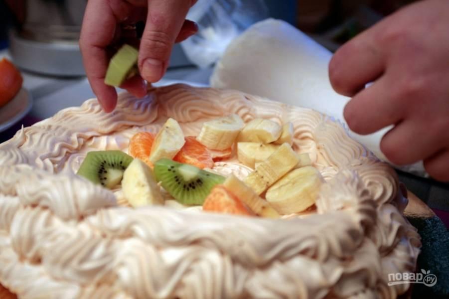 Фрукты промойте, очистите. Затем нарежьте их крупными кусочками. Разложите фрукты в меренгу.