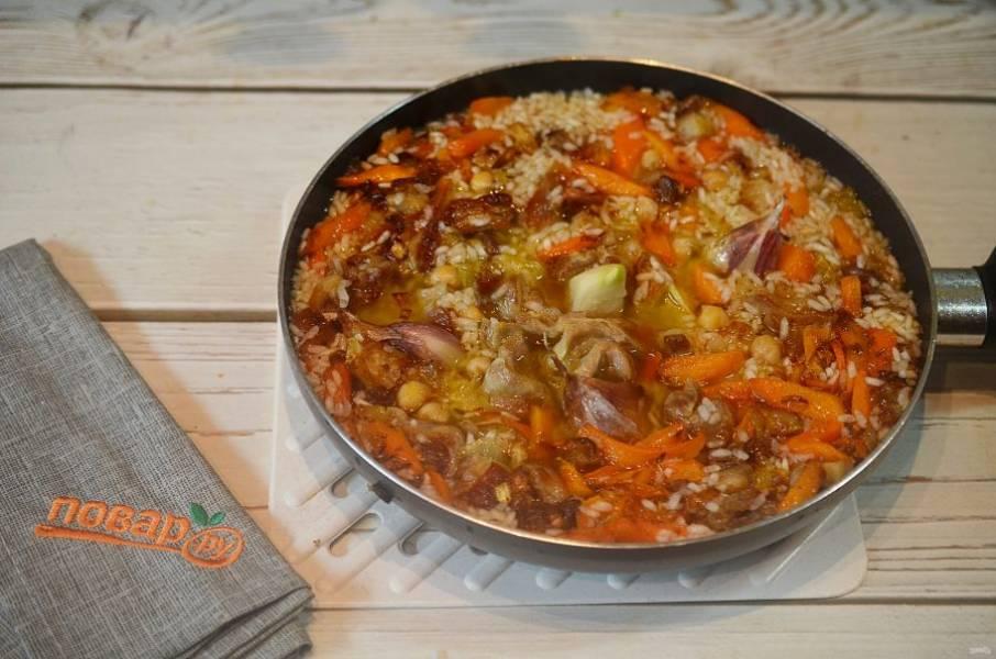 14. Залейте водой, чтобы она была на 1,5 см. выше риса. Доведите до кипения, затем уменьшите огонь, накройте крышкой и готовьте до готовности.