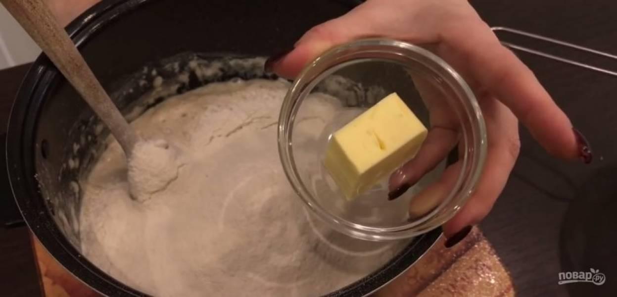 4.  К опаре просейте всю оставшуюся муку и растопленное сливочное масло (не горячее). Оставьте тесто на 30 минут при комнатной температуре. Муку для замеса высыпьте на стол, выложите тесто и обомните его.
