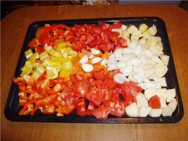 Заранее отварите говядину. На противне разложите порезанные перцы, помидоры, картофель, морковь и лук, а также дольки чеснока.