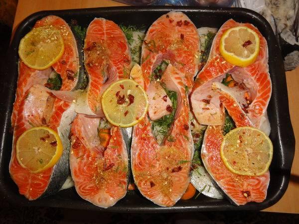 Оставшийся лимон нарезаем на тонкие колечки и раскладываем поверх рыбы.