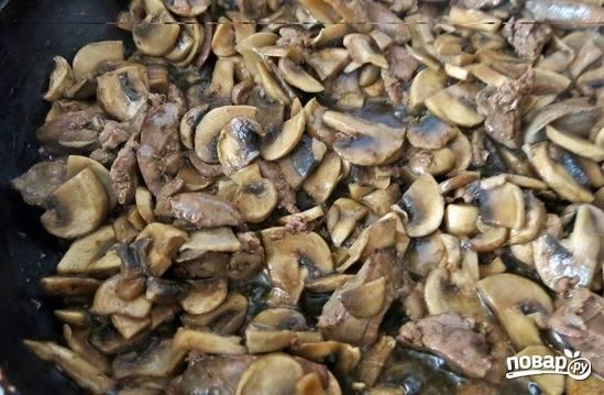 Грибы вымойте и обсушите. Нарежьте их на четвертинки. Выложите грибочки к печени и дождитесь, пока они пустят свой сок. Затем слегка поджарьте грибы.
