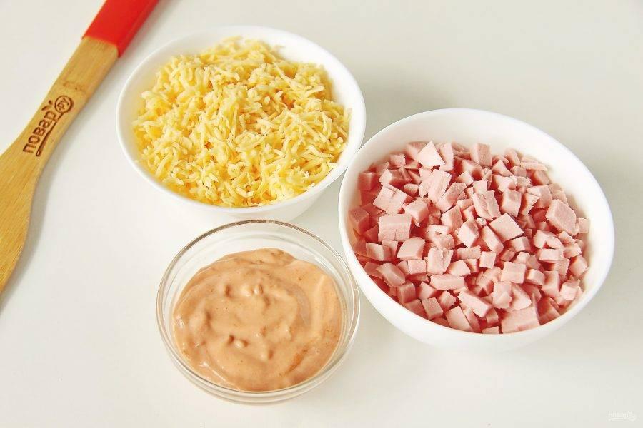 Пока тесто поднимается, подготовьте начинку. Для соуса соедините кетчуп и майонез. Колбасу нарежьте мелкими кубиками. Сыр натрите на мелкой терке.