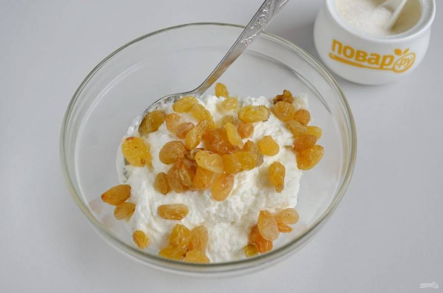 4. Отложите половину творожной массы в тарелочку, добавьте распаренный изюм и ванильный сахар, перемешайте.