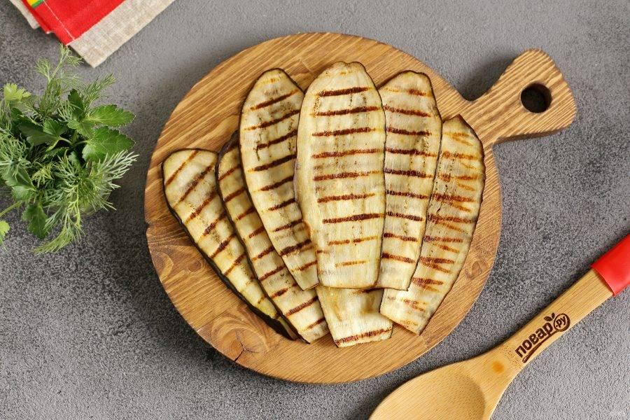 Смажьте каждую полоску маслом и обжарьте с двух сторон на сковороде гриль (можно запечь в духовке). Наша задача не приготовить баклажаны, а сделать их более мягкими и гибкими.