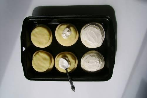 14. Выложите тесто на противень. Из картофельных шариков сделайте чуть меньшие по объему лепешки, выложите их сверху. Смажьте сметаной со всех сторон, отправьте в разогретую духовку минут на 25.  Вот такой аппетитный и несложный вариант, как сделать бабушкины шаньги.