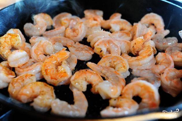 4. Приготовить креветки. Нагреть рапсовое масло в тяжелой сковороде на сильном огне. Добавить креветки, перемешать и жарить, пока они не перестанут быть прозрачными.