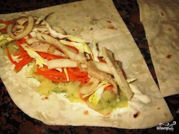 Выложите слоями сначала картофель, потом морковку с капустой, а сверху — кальмары.