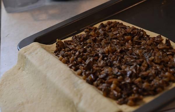 3. Тесто раскатайте довольно тонко и выложите на смазанный маслом противень так, чтобы лежала примерно половина. Распределите по всей поверхности (оставив немного места по краям) начинку. При желании можно добавить немного зелени, например.