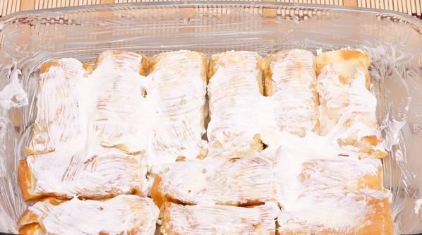 6. Жаропрочную форму как следует смазать сливочным маслом и выложить блины. Если хотите сделать сладкие блинчики с творогом в духовке в домашних условиях, в сметану можно дополнительно добавить сахар. Смазать блины сметаной и отправить в разогретую духовку минут на 15. Перед подачей можно присыпать блины сахарной пудрой, какао или полить сгущенкой.
