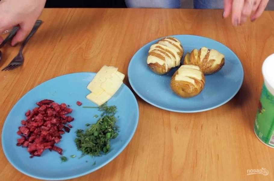 3. Посолите картофель и поместите его в разогретую до 180 градусов духовку на 20 минут. Мелко нарежьте бекон или колбасу и поджарьте на сковороде. Сыр нарежьте тонкими пластинками и нафаршируйте им картофель, когда он будет готов.