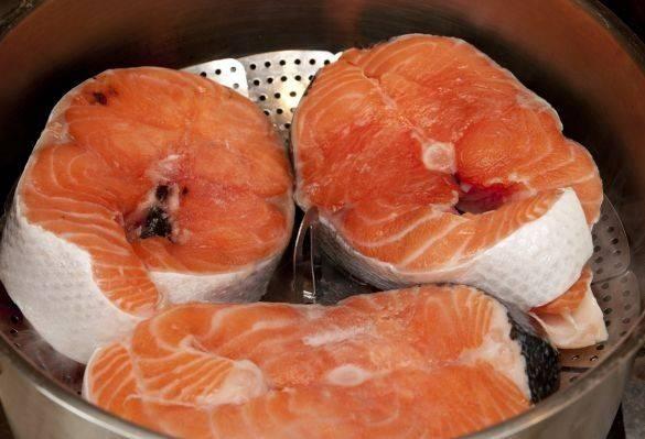 Готовить рыбу будем на пару. Если у вас нет пароварки - не беда, можно воспользоваться специальными вставками для обычных кастрюль или использовать дуршлаг. Смазываем маслом поверхность, на которой будем готовить стейки, и выкладываем рыбу.