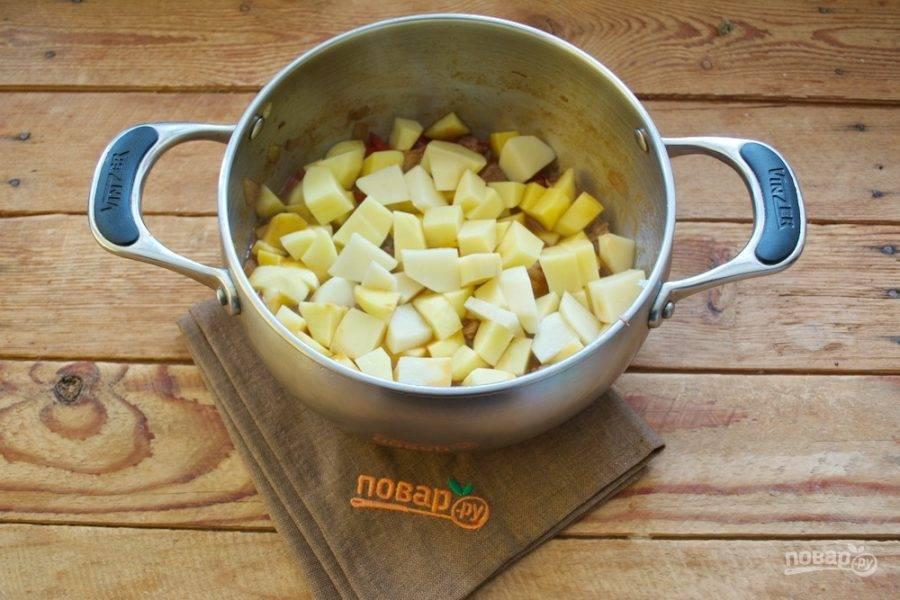Очистите картофель. Нарежьте кубиком и добавьте в кастрюлю.