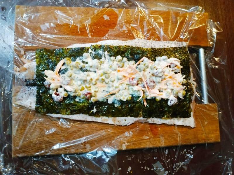 Выложите начинку поверх листа нори и аккуратно распределите по всей рыбке.