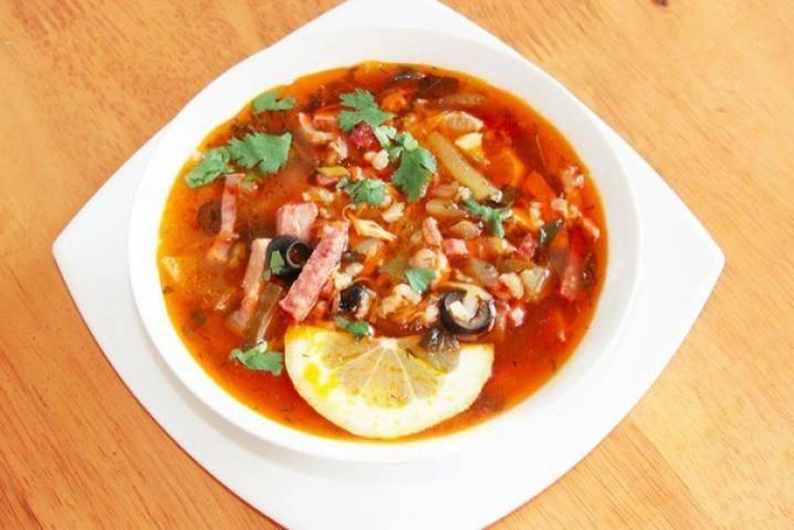 Готовую солянку с томатной пастой подавайте с ломтиками лимона и сметаной. Приятного аппетита!