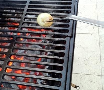 Мясо в принципе готово, поэтому самое время заняться грилем, первым делом очищаем его решетки, затем разжигаем огонь. С тарелку наливаем немного растительного масла и пускаем в него половинку луковицы. Перед тем как выкладывать мясо на решетку, ее следует протереть хорошенько этой луковицей в масле.