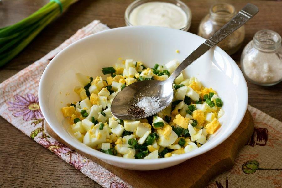 Соедините в миске нарезанные яйца и лук, всыпьте соль и перец по вкусу.