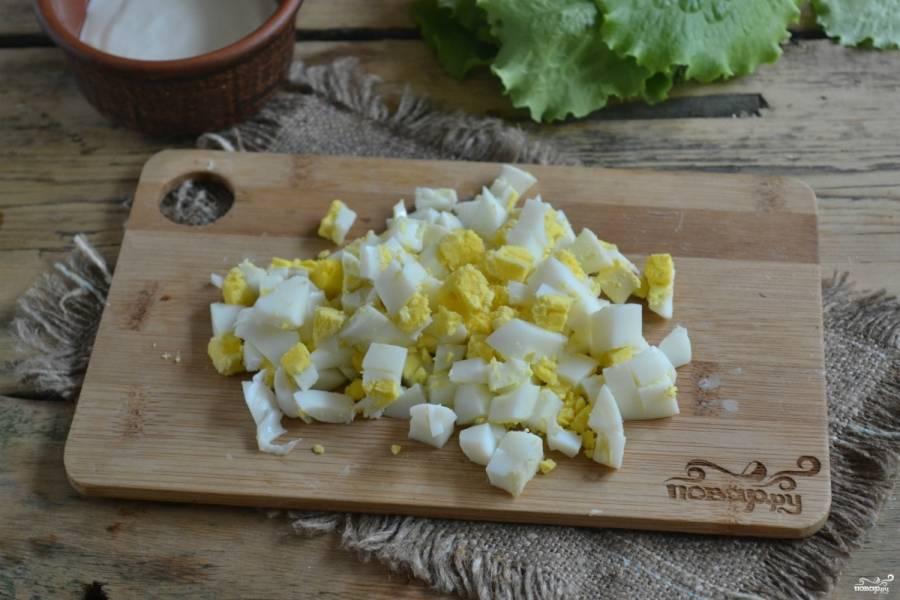 Отдельно в сотейнике поставьте вариться яйца. Это займет 10 минут. Затем слейте горячую воду, залейте холодной и почистите от скорлупы. Яйца измельчите и добавьте в борщ. В конце варки положите щавель, заправьте всё сметаной. Дайте прокипеть пару минут — и снимайте с огня.
