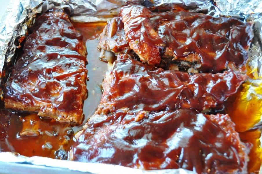 Промажьте ребрышки соусом и укройте фольгой. Отправьте в духовку с температурой 200 градусов на 1,5 часа.