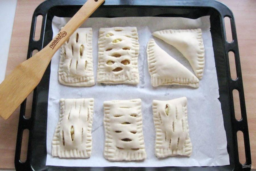 Также поступите с остальным тестом и начинкой. Можно сделать несколько вариантов пирожков. Выложите ваши турноверы на противень с пергаментом для выпечки.