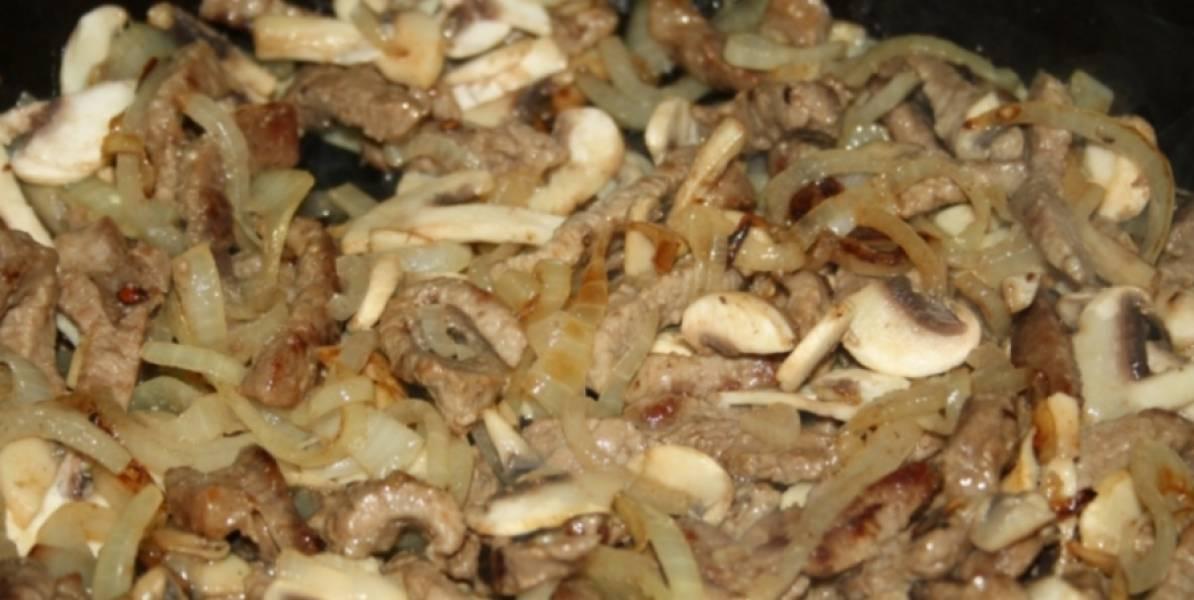 Затем добавляем лук порезанный полукольцами и измельченный чеснок. Жарим до румяности. Добавляем шампиньоны, порезанные тонкими пластинками. Готовим еще 3-4 минуты.