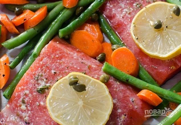 4. Выложите ингредиенты на противень. Сверху влейте масло. На рыбу положите по кружку лимона и каперсы.