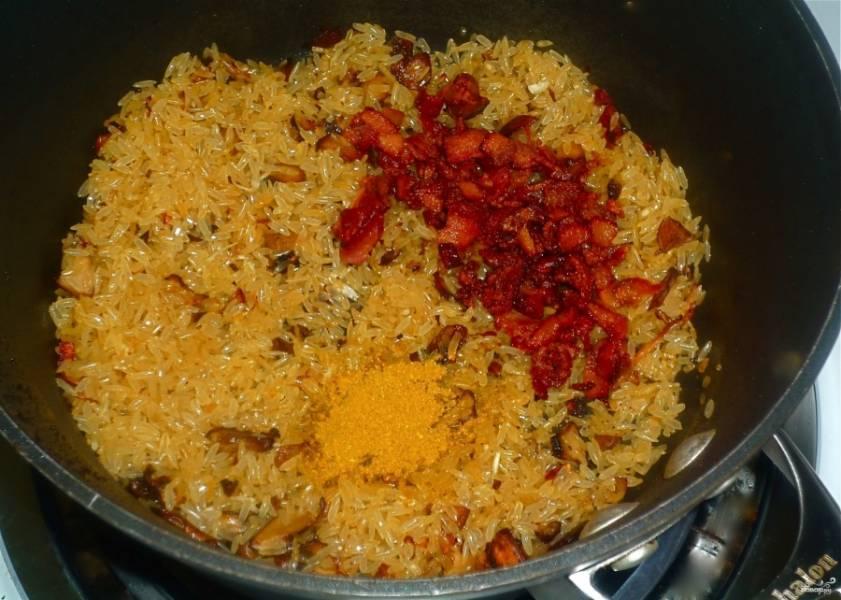 2. Добавим теперь промытый рис, обжарим все вместе, пока рис не станет румяным. Всыпаем теперь все специи, добавим морковь кружочками и заливаем все ингредиенты кипятком. На маленьком огне под крышкой тушим 40 минут.