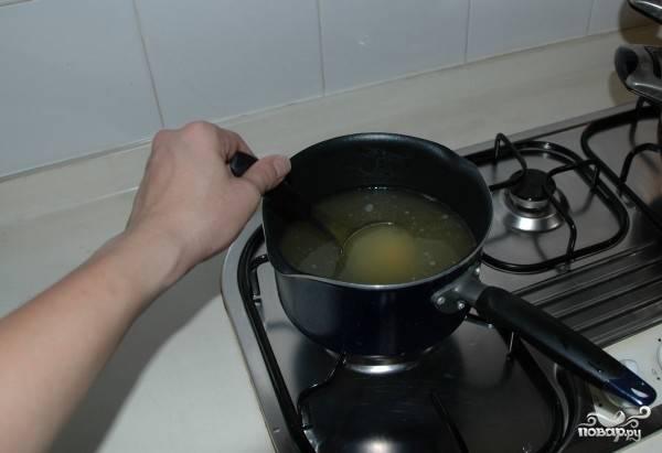 4. Получается около двухсот миллилитров сока, который смешиваем в сотейнике с кипяченой водой. Если имбирного сока получилось меньше, то рассчитываем пропорцию 1:3 (воды в три раза больше сока). Ставим сотейник на небольшой огонь, доводим воду до кипения. Как только закипит, делаем самый маленький огонь, а после добавляем мед или сахар. Все тщательно перемешиваем до полного растворения и выключаем огонь.