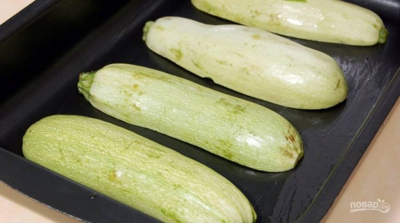Выложите половинки кабачков на противень смазанный маслом. Запекайте его в духовке 10-15 минут при 180 градусах.