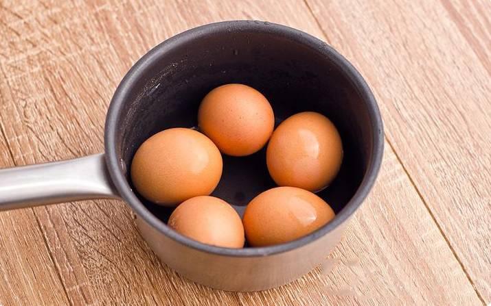 Яйца варим вкрутую. Очищаем их от скорлупы и режем очень мелким штрихом. Открываем кукурузу, сливаем сливаем с неё в раковину жидкость.