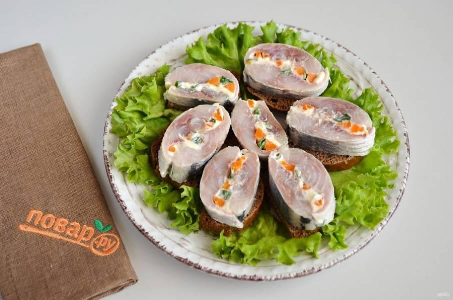 8. Порежьте ломтиками черный хлеб. Достаньте селедочный рулет, острым ножом порежьте на кусочки. На блюдо положите зелень, потом хлеб с селедочкой.