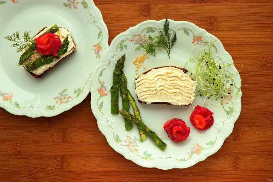 Теперь можно собирать сморреброд. Кусочек хлеба намажьте сливочным сыром с хреном. Сверху выложите спаржу, рыбу, украсьте поджаренным кунжутом и любой зеленью на ваш вкус.