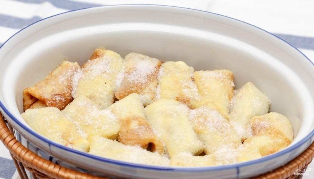 3. Отдельно смешаем творог и мед, добавим ягоды и крахмал, аккуратно перемешаем, стараясь не подавить ягодки. Этой смесью начиняем блины, складываем их в глубокую кастрюлю, присыпаем сверху сахаром и смазываем сливочным маслом. Под крышкой в духовке держим примерно 20 минут при 170- градусах.