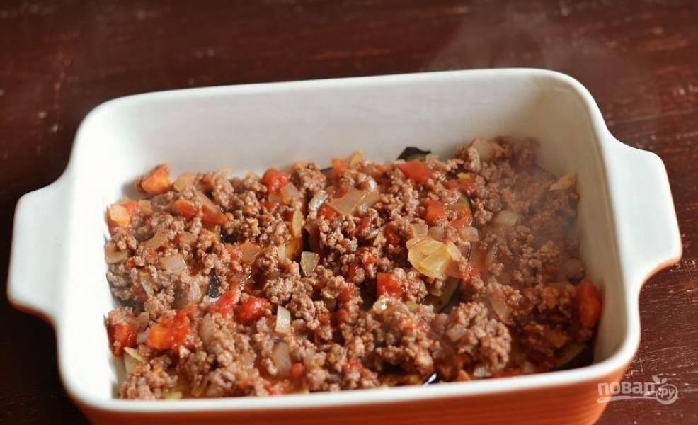 Затем поверх баклажанов выложите мясной соус. Снова распределите слой баклажанов и слой мяса.