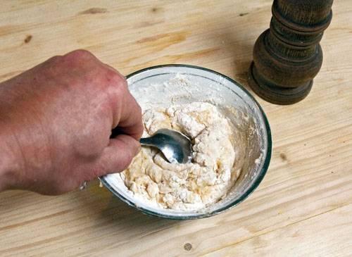 4. Теперь необходимо приготовить тесто. Для этого нужно вбить в миску яйцо и добавить соль. Немного взбить и влить около 100 миллилитров холодной воды. Тщательно перемешать и сразу добавить около 150 грамм муки. Вымешивать тесто, периодически подсыпая муку. Тесто должно быть крутым и плотным.