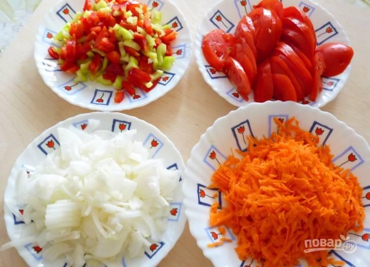 Моем овощи и нарезаем перец и лук мелкими кусочками, морковь трем на терке, помидоры режем дольками. Картофель режем крупным кубиком.