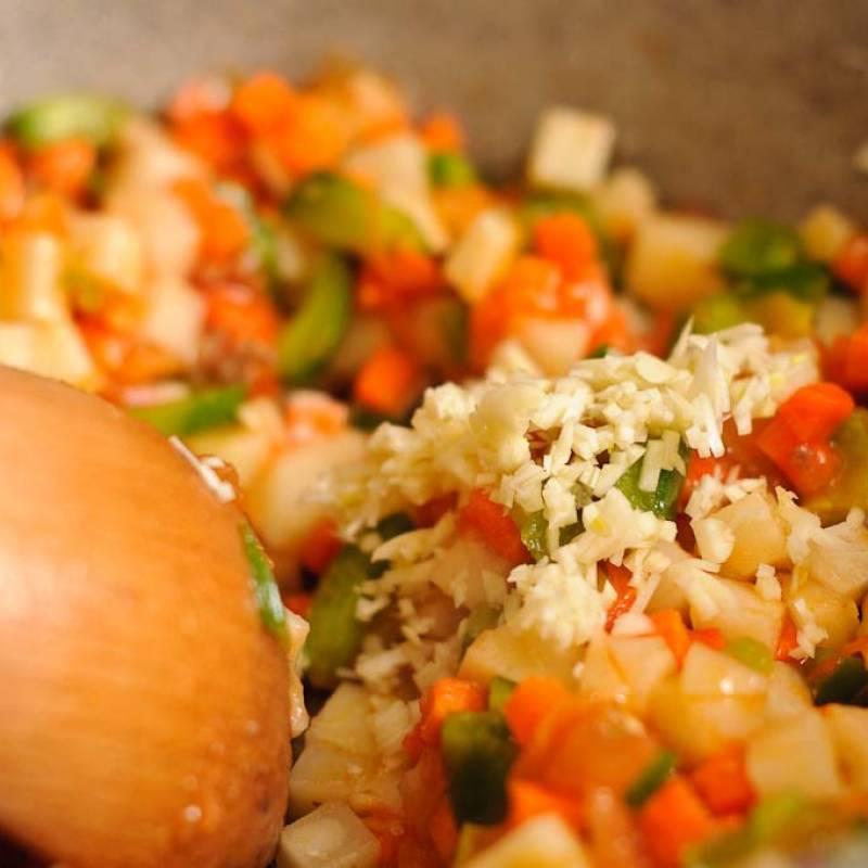 Добавить чеснок и перемешать овощи еще пару раз.