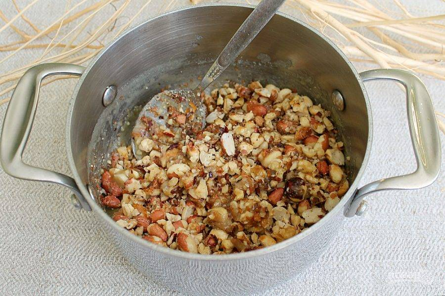 Орехи высыпаем в кастрюлю и перемешиваем вместе со сладкой массой.  Ставим кастрюлю в холод на 15 минут.