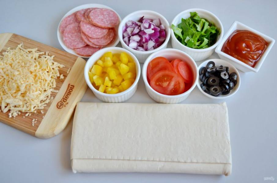 Разморозьте слоеное тесто при комнатной температуре. Колбасу и помидоры порежьте кружочками, лук и сладкий перец кубиками. Шпинат полосочками, оливки колечками. Сыр на крупной терке.