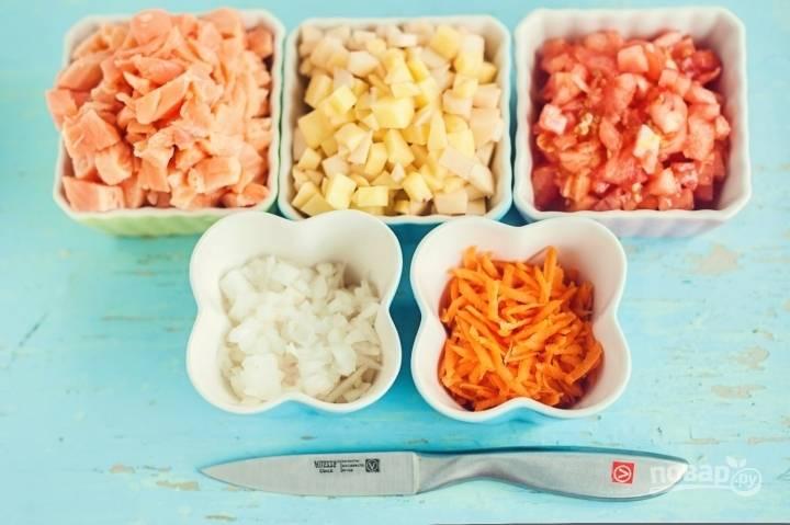 Сначала нужно измельчить все ингредиенты. Сёмгу, картофель и лук нарежьте кубиками. Морковь и помидоры натрите на тёрке.