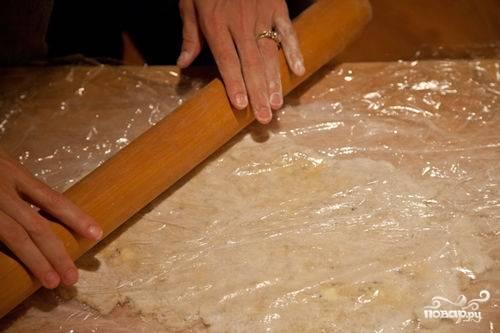 Теперь используем большое количество муки, чтобы тесто не прилипло к столешнице и к скалке. Можно тесто накрыть пищевой пленкой и раскатывать до нужной формы дна. Однако тесто надо раскатать немного больше, чтоб остались края (по 2-3 см).