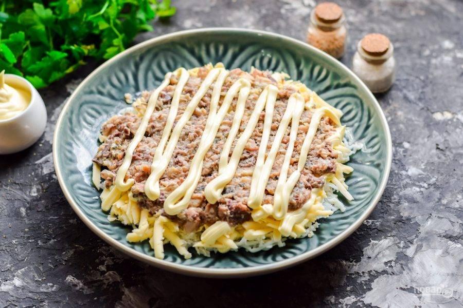 Рыбные консервы разомните вилкой, выложите поверх сыра, слегка смажьте майонезом.