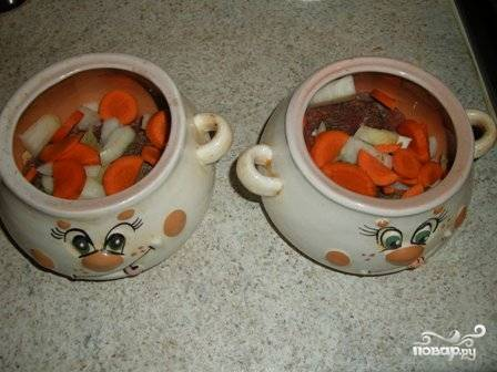Репчатый лук чистим и нарезаем четвертинками, морковь режем кружочками. Выкладываем нарезанные овощи в горшочки.