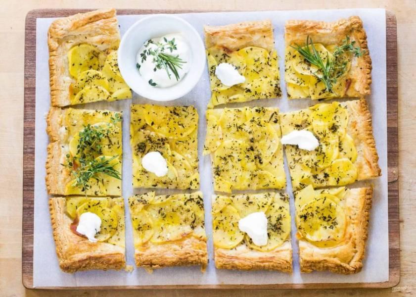 6.Немного остудите пирог, посыпьте его оставшейся ложкой трав, солью и перцем. Разрежьте пирог на кусочки и подавайте со сметаной.